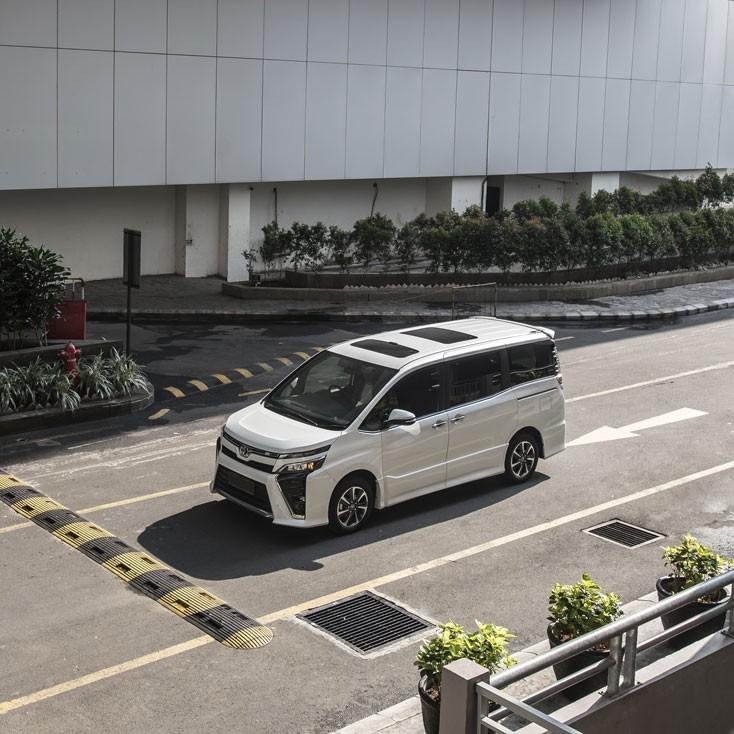 gambar menunjukkan sebuah mobil Toyota All New Voxy berwarna putih sedang berkendara di jalan