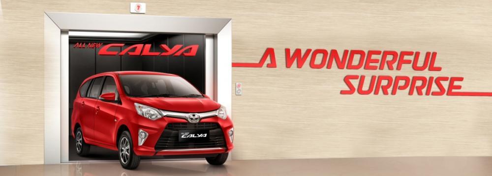 gambar menunjukkan sebuah mobil Toyota Calya berwarna merah sedang diparkir di depan gedung