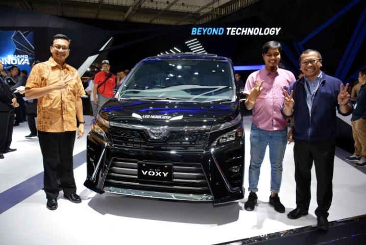 gambar menunjukkan sebuah Toyota All New Voxy berwarna hitam sedang ada dalam sebuah pameran otomotif