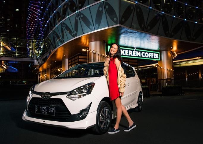 gambar menunjukkan seorang wanita sedang disamping sebuah mobil Toyota New Agya 2018 berwarna putih sedang diparkir di jalan