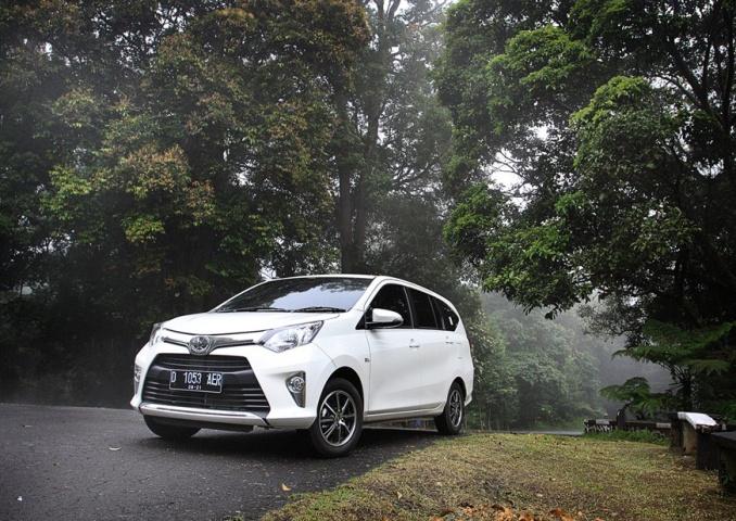 gambar menunjukkan sebuah mobil Toyota Calya berwarna putih sedang berkendara di jalan