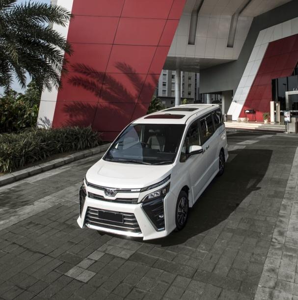 gambar menunjukkan sebuah mobil Toyota All New Voxy berwarna putih sedang diparkir di depan gedung