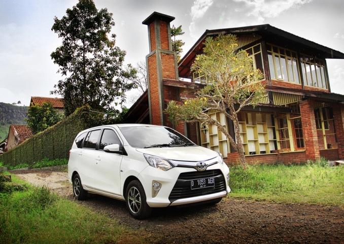 gambar menunjukkan sebuah mobil Toyota Calya berwarna putih sedang diparkir di depan rumah