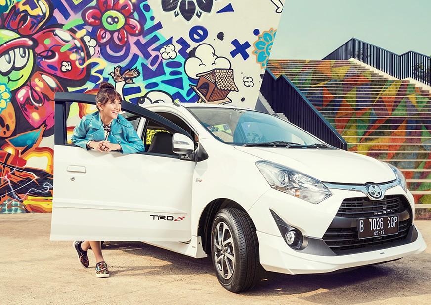 gambar menunjukkan seorang wanita sedang di samping sebuah mobil Toyota New Agya 2018 berwarna putih sedang diparkir di jalan