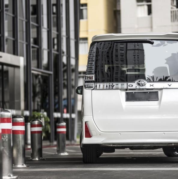gambar menunjukkan sebuah mobil Toyota All New Voxy berwarna putih dilihat dari belakangnya