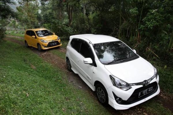gambar menunjukkan duamobil Toyota New Agya berwarna putih dan kuning sedang berkendara di jalan