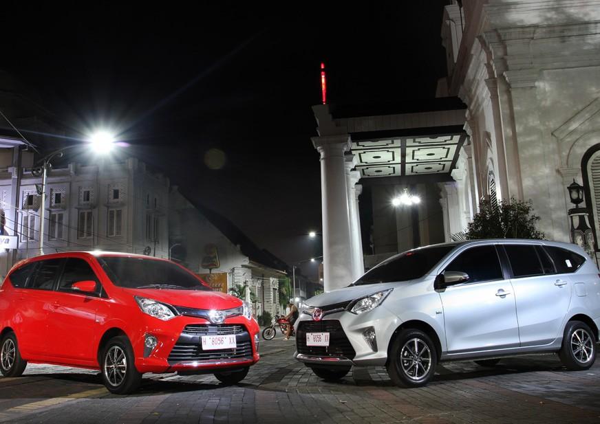 gambar menunjukkan dua mobil Toyota Calya berwarna putih dan merah sedang diparkir di jalan