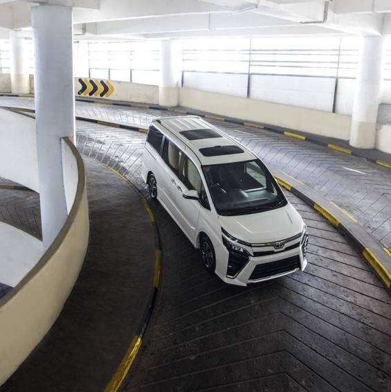 gambar menunjukkan sebuah mobil Toyota All New Voxy berwarna putih sedang berkendara dalam parkir basement