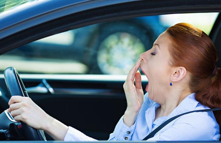 Gambar ini menunjukkan seorang wanita di dalam mobil sedang mengantuk