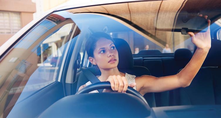 Gambar ini menunjukkan seorang wanita dalam mobil sedang memegang kemudi dan spion tengah