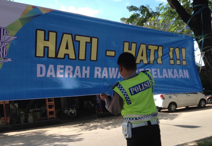 Gambar ini menunjukkan seorag polisi sedang memegang sedang memegang spanduk bertuliskan hati-hati daerah rawan kecelakaan
