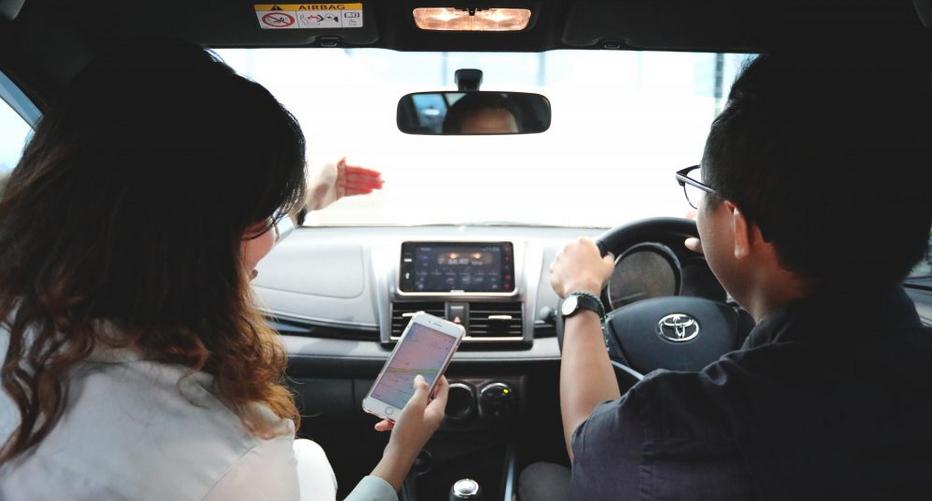 gambar ini menunjukkan 2 orang di dalam mobil satu mengemudi satu membawa ponsel