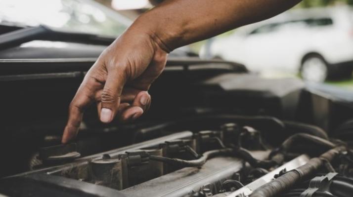 Gambar ini menunjukkan sebuah tangan menunjuk pada komponen mesin mobil