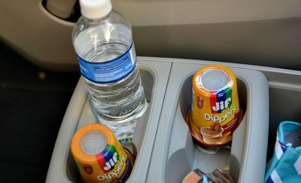 Gambar ini menunjukkan minuman dalam botol dan 2 dalam gelas plastik di tempat minum pada mobil