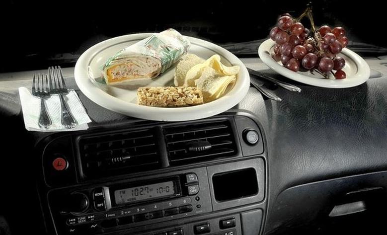 Gambar ini menunjukkan 2 garpu dan makanan di atas piring dan anggur disampingnya di atas dashboard mobil