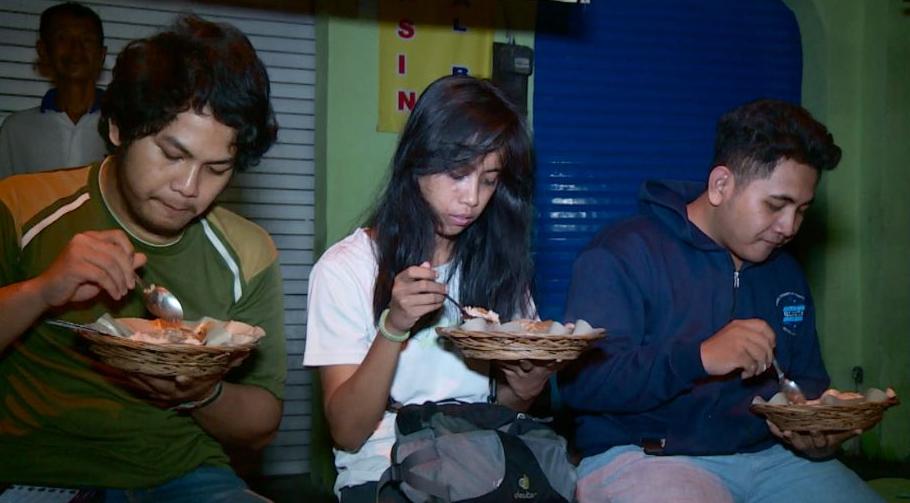 Gambar ini menunjukkan 2 orang pria dan 1 wanita sedang bersantap makanan saat sahur