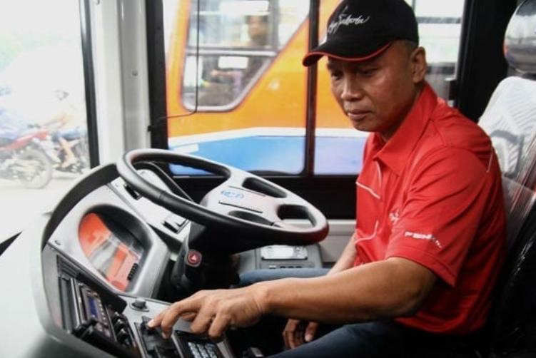 Gambar ini menunjukkan seorang supir bus dengan baju merah sedang menekan tombol
