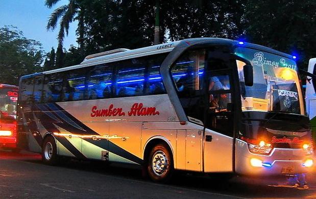 Gambar ini menunjukkan sebuah mobil bus di malam hari dengan lampu menyala