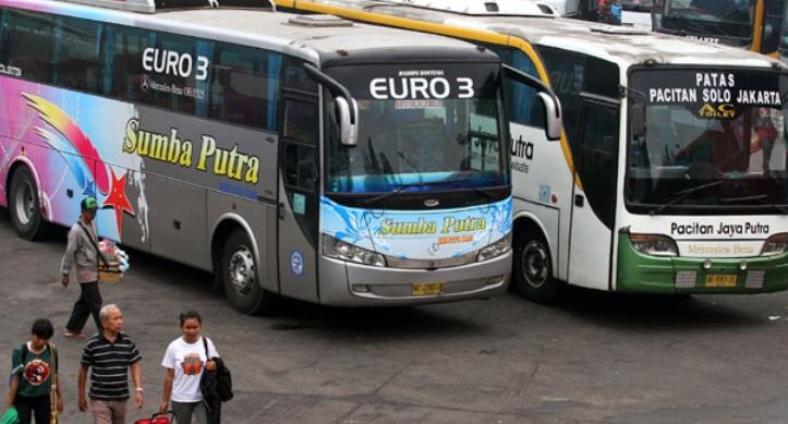 Gambar ini menunjukkan 2 buah bus sedang terparkir di terminal mobil dan beberapa orang sedang berjalan di dekatnya