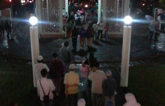 Gambar ini menunjukkan banyak orang sedang berjalan menuju masjid untuk sholat tarawih