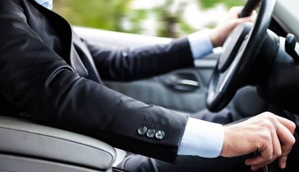 Gambar ini menunjukkan pengemudi mobil dengan tangan di kemudi dan tuas perseneling