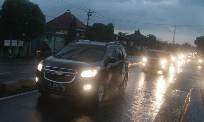 Gambar ini menunjukkan beberapa mobil sedang melaju di jalan di pagi hari dengan lampu menyala