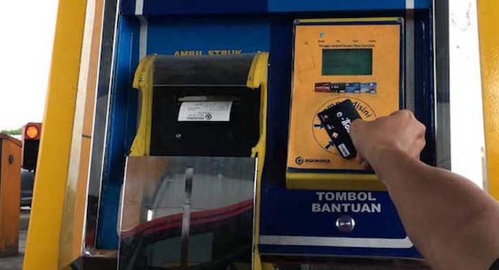 Gambar ini menunjukkan sebuah tangan memegang kartu tol sedang dimasukkan mesin tempat membayar tol