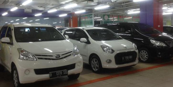 Gambar ini menunjukkan 2 mobil warna putih dan 1 warna hitam sedang terparkir berjejer
