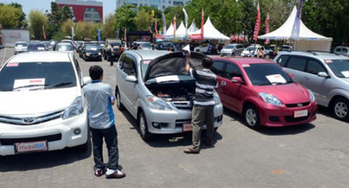 Gambar ini menunjukkan 2 orang pria sedang memeriksa mesin mobil dan banyak mobil lain di sekitarnya