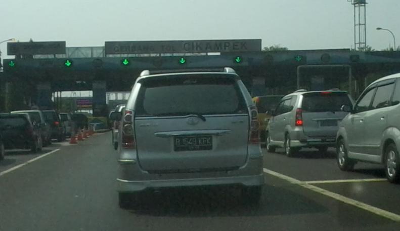 Gambar ini menunjukakkan mobil warna putih dan beberapa mobil sedang mengantri di gerbang jalan tol