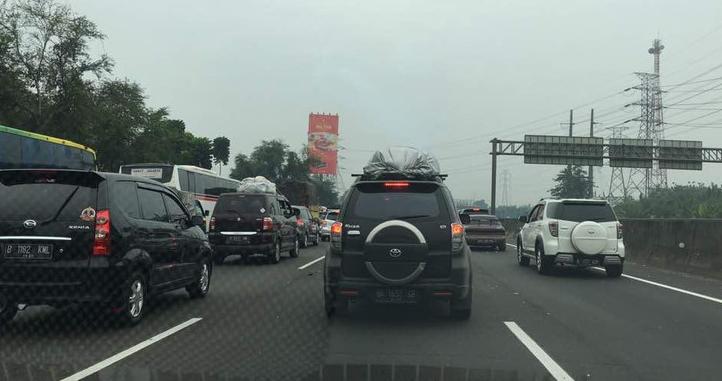 Gambar ini menunjukkan beberapa mobil sedang menempuh perjalanan dengan berbagai merek