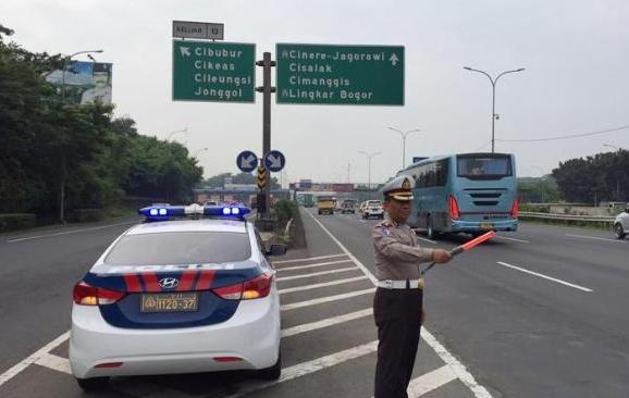 Gambar ini menunjukkan sebuah mobil polisi dan seorang petugas sedang mengatur lalu lintas jalan