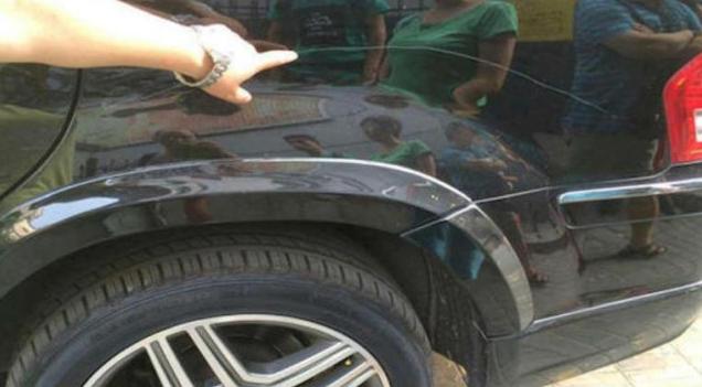 Gambar ini menunjukkan sebuah tangan sedang menunjuk goresan pada bodi mobil warna hitam