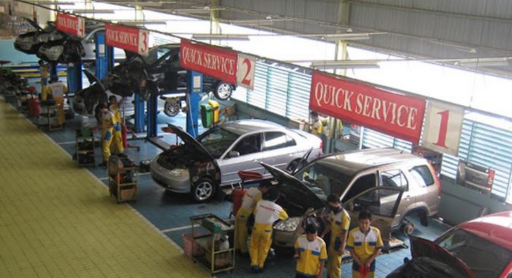 Gambar ini menunjukkan sebuah bengkel dengan beberapa mekanik sedang memeriksa kendaraan
