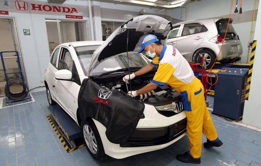 Seorang mekanik sedang memeriksa mobil di bengkel resmi Honda
