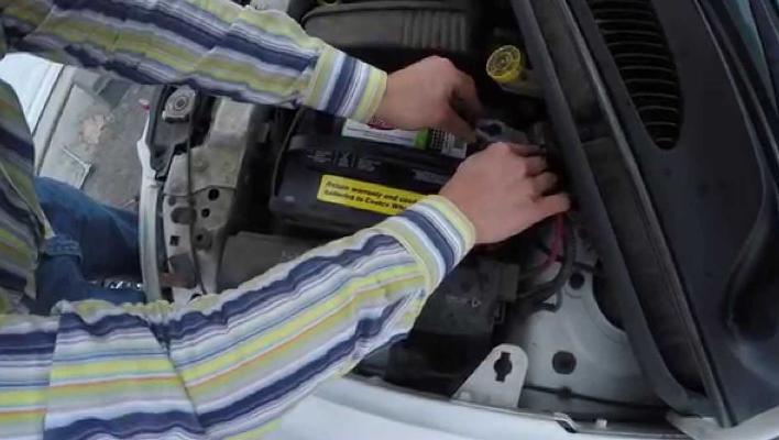 Gambar ini menunjukkan dua buah tangan sedang memegang kutub aki mobil