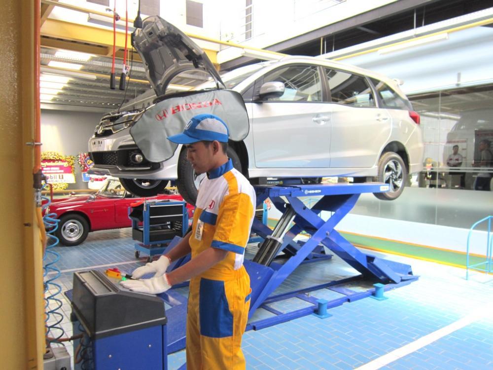 Seorang mekanik Honda sedang mengecek kondisi mobil melalui sistem komputer