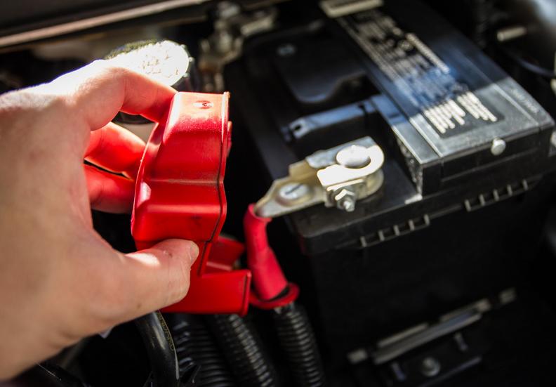 Gambar ini menunjukkan sebuah tangan memegang tutup kutub aki mobil warna merah