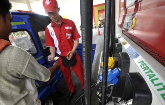 Gambar ini menunjukkan seorang konsumen membayar bahan bakar pada petugas spbu