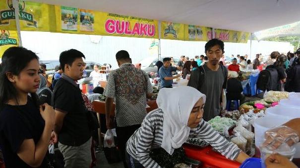 Gambar ini menunjukkan beberapa orang sedang mengantri untuk membeli makanan dan minuman untuk buka puasa