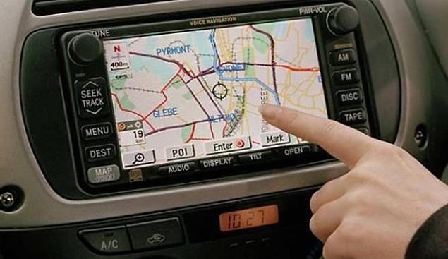 Gambar ini menunjukkan jari telunjuk menempel pada layar GPS Mobil