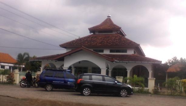 Gambar ini menunjukkan sebuah masjid dengan 2 buah mobil di depannya