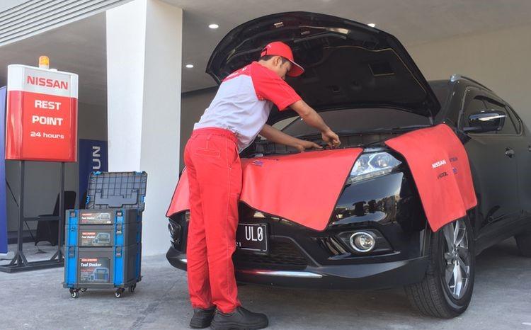 Seorang teknisi sedang memeriksa mobil di Nissan Rest Point
