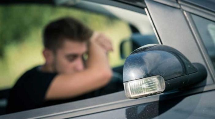 gambar ini menunjukkan seorang pengemudi terlihat samar tidur di dalam kendaraan