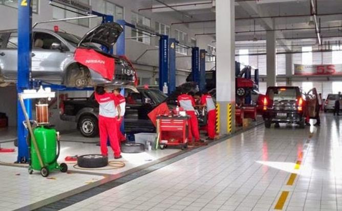 gambar ini menunjukkan beberapa mekanik sedang memeriksa kendaraan di bengkel resmi