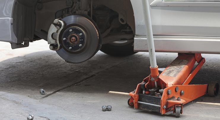 gambar ini menunjukkan sebuah mobil dengan ban terlepas sedang didongkrak