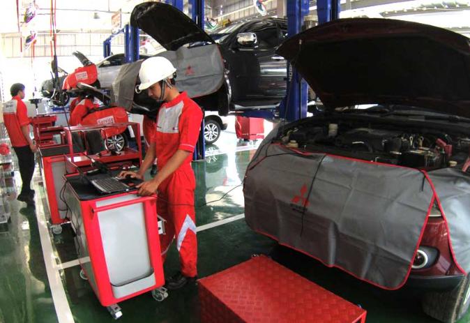 Gambar ini menunjukkan seorang mekanik bengkel sedang memeriksa kondisi mobil