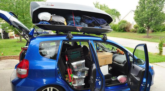 Gambar ini menunjukkan sebuah mobil lcgc w3arna biru dengan diisi banyak barang melebihi kapasitas