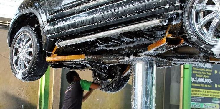 gambar ini menunujukkan sebuah mobil warna hitam diangkat menggunakan lift sedang dicuci