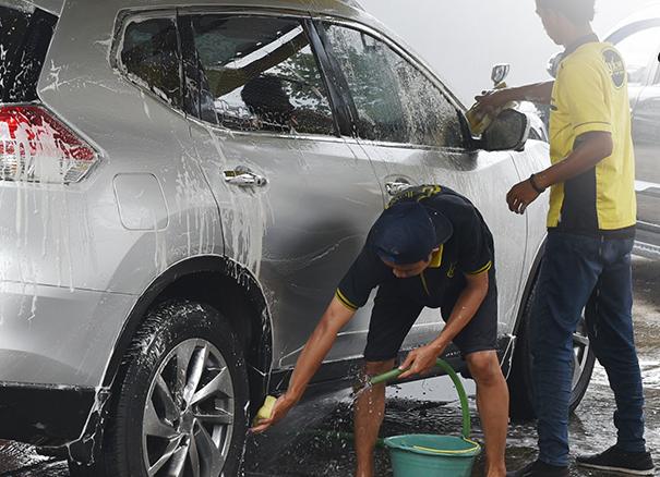 gambar ini menunjukkan 2 orang sedang mencuci mobil warna silver